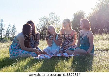 Group of Girls Sitting Together in Grassy Field With Sunlight Overhead #618877514