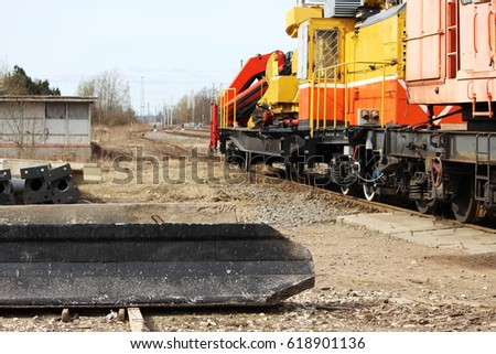 Reinforced concrete piles lie on the ground after unloading with a loader on the railway. #618901136