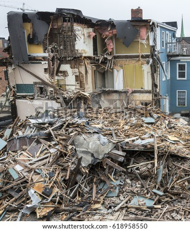 A partially destroyed building. Most of the building lies as a pile of rubble next to the building. Sky is overcast.  #618958550