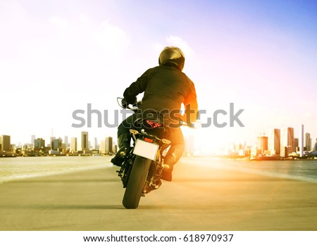 rear view of man riding motorcycle on urban traffic road for people leisure traveling theme #618970937
