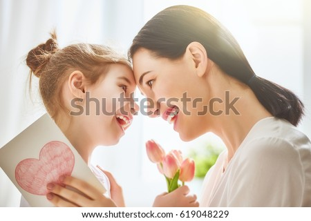 Happy mother's day! Child daughter congratulates mom and gives her flowers tulips and postcard. Mum and girl smiling and hugging. Family holiday and togetherness. Royalty-Free Stock Photo #619048229