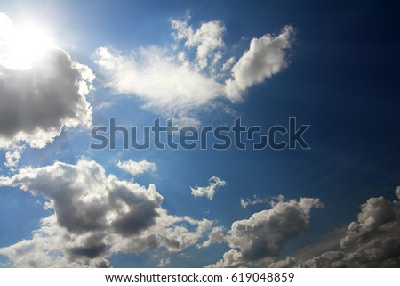 dramatic scene with clouds and sun on blue sky Royalty-Free Stock Photo #619048859