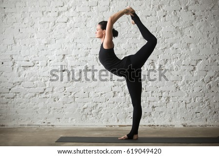 Young yogi attractive woman practicing yoga concept, standing in Natarajasana exercise, Lord of the Dance pose, working out, wearing sportswear, black tank top and pants, full length, loft background  #619049420