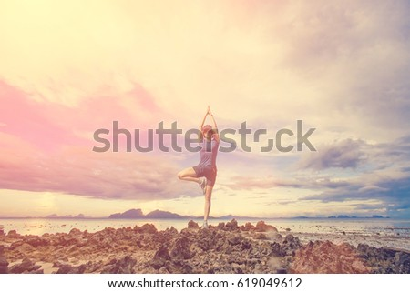 The woman is engaged in yoga on a background of rocks, the sea and sky. Toned #619049612