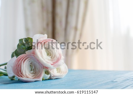 Beautiful flower bouquet pink radunculus and eucalyptus on the blue wooden table background