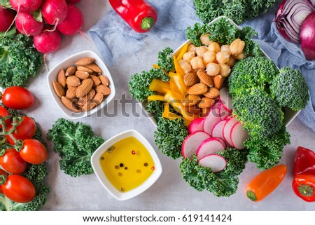 Health care, diet and nutrition concept. Buddha bowl with vegetables and nuts on a rustic table, vegetarian vegan raw balanced detox meal food. Flat lay top view overhead #619141424