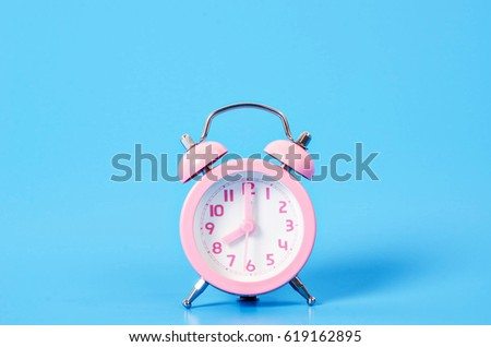 Vintage pink alarm clock on blue background with copy space. #619162895