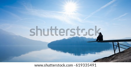 The woman is sitting on the pier. Self reflection. Bright sun in the blue sky. Royalty-Free Stock Photo #619335491