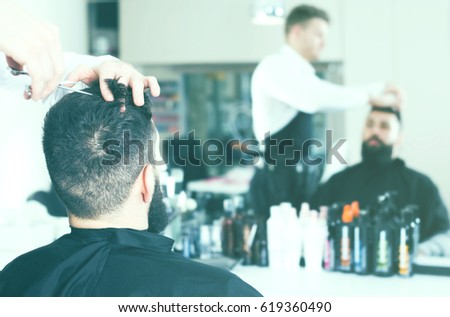 professional male stylist creating new haircut for man client at hairdressing salon #619360490