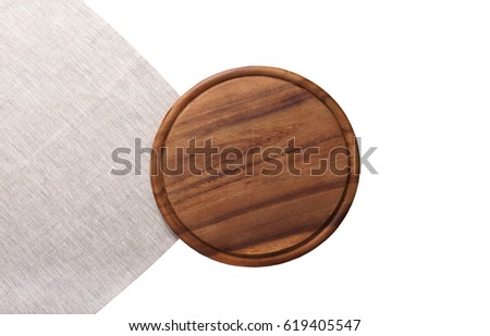 Brown round cutting pizza board for holiday dishes on gray linen napkin isolated on white. Top view and mock up #619405547