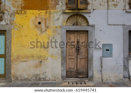 old weathered and abandoned facade of a residential building in Italy #619445741