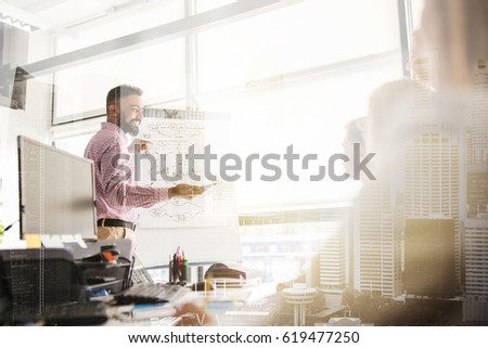 business, startup, presentation, strategy and people concept - man showing scheme on flipboard to creative team at office over urban double exposure effect
