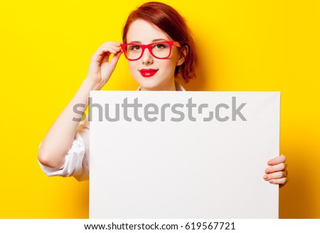 photo of beautiful young woman holding empty poster on the wonderful yellow studio background #619567721