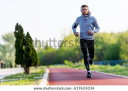 Man jogging in the morning out on the race track Royalty-Free Stock Photo #619624334