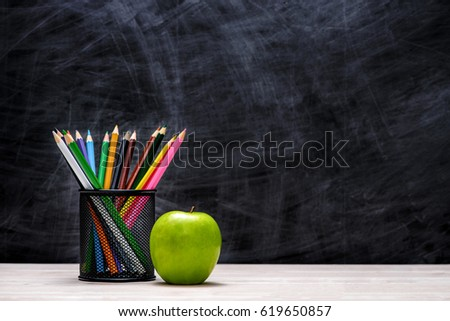 School and office supplies and apple in front of blackboard. #619650857