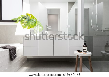 Luxury white family bathroom styled with greenery and a wooden s