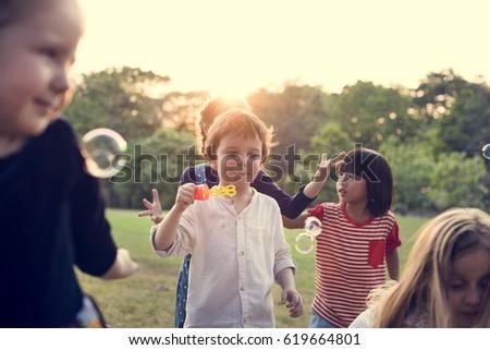 Group of kindergarten kids friends playing blowing bubbles fun #619664801