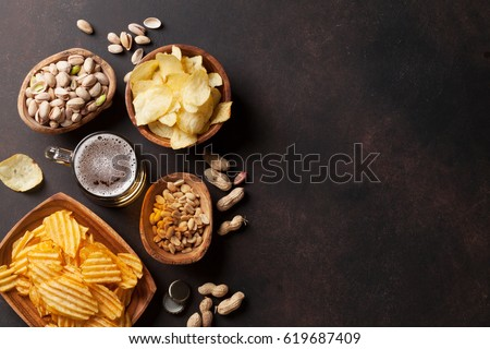 Lager beer and snacks on stone table. Nuts, chips. Top view with copyspace Royalty-Free Stock Photo #619687409