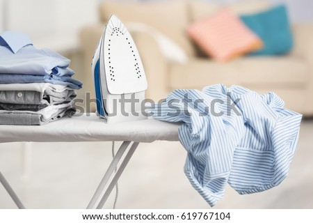 Electric iron and pile of clothes on ironing board Royalty-Free Stock Photo #619767104