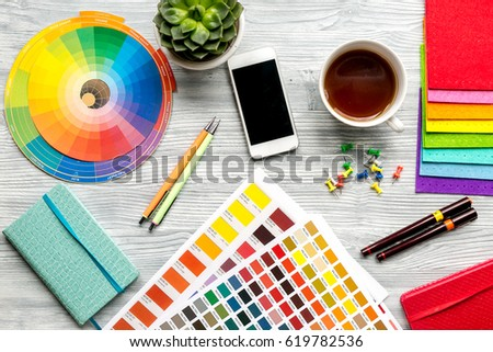 designer tools, cup and mobile on work table white background top view