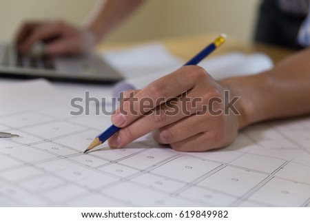 Architect or engineer working on blueprint and laptop at workplace - architectural project, Construction concept. #619849982