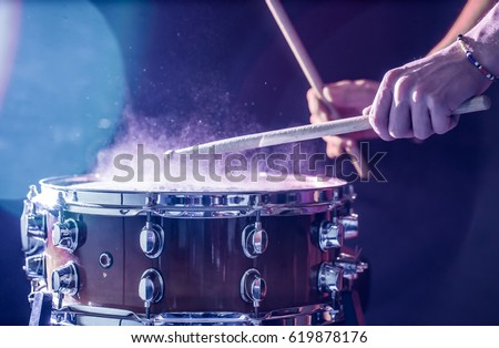 man plays musical percussion instrument with sticks closeup on a black background, a musical concept with the working drum, beautiful lighting on the stage Royalty-Free Stock Photo #619878176