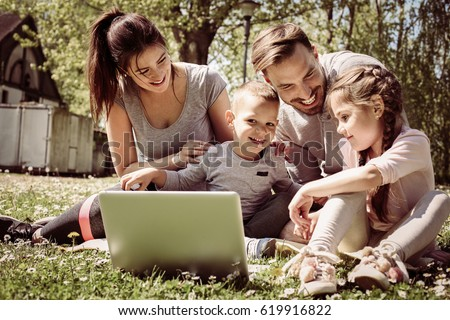 Happy family using laptop, sitting on the  grass. #619916822