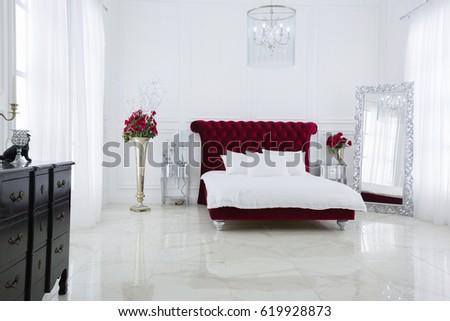 Luxury white light bedroom interior design. Dark red large bed #619928873