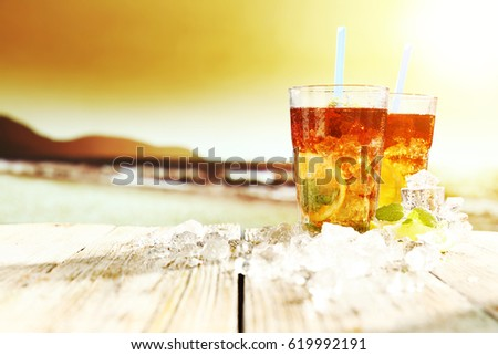 Summer sunset on beach and photo of ice tea on desk with ice and free space for your decoration