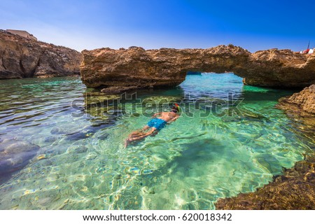 Blue Lagoon, Malta - Snorkeling tourist at the caves of the Blue Lagoon on the island of Comino on a bright sunny summer day with blue sky #620018342