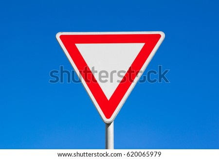 Give way / Yield - red and white triangle. Clear blue sky is behind road sign.