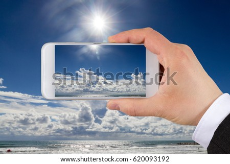Taking pictures with smart phone of beautiful beach with blue sky and clouds.