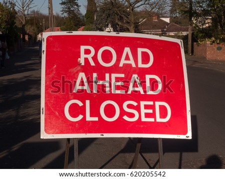 A a big red and white road closed ahead sign #620205542