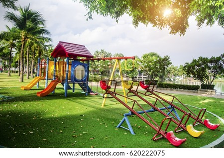 Children playground on yard activities in public park surrounded by green trees at sunlight morning. Children run, slide, swing,seesaw on modern playground. Urban neighborhood childhood concept. Royalty-Free Stock Photo #620222075
