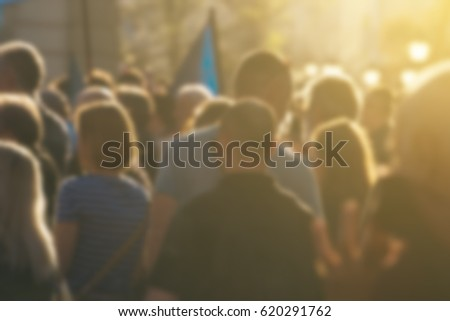 Large group of unrecognizable people as audience to politician's speech outdoors, defocused crowd attending political meeting #620291762