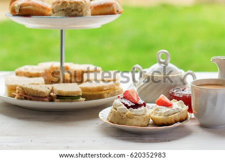 English afternoon teas in the garden cafe: scones with clotted cream and jam, strawberries, with various sandwiches on the background, selective focus Royalty-Free Stock Photo #620352983