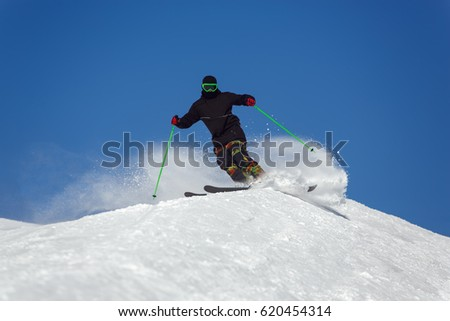 Skier in mountains, prepared piste and sunny day #620454314