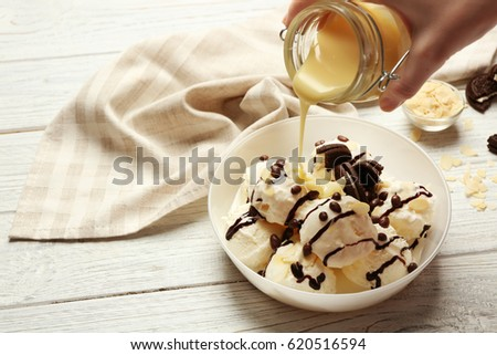 Pouring sauce onto delicious dessert with ice cream in bowl #620516594