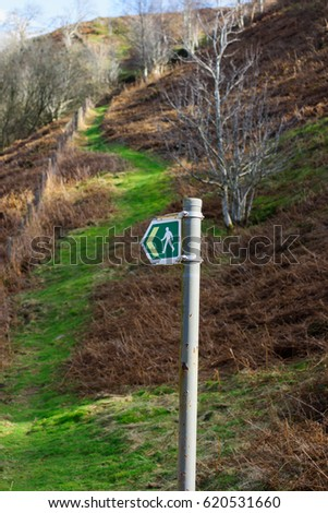 Rural sign post for hiking trails with a green grassy path leading up a British hillside #620531660