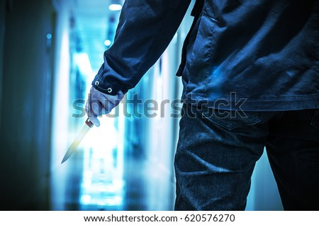 Evil criminal with sharp knife ready for robbery or to commit a homicide with clipping path #620576270
