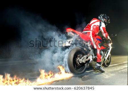 VINNITSA, UKRAINE - OCTOBER 3, 2012: Sexy biker man standing with red sport motorcycle Honda CBR Fireblade 1000RR #620637845