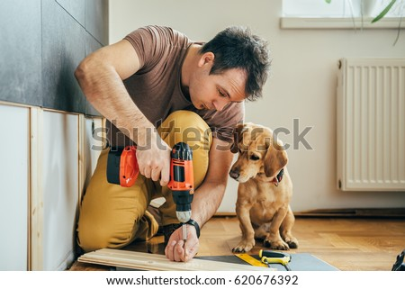 Man doing renovation work at home together with his small yellow dog Royalty-Free Stock Photo #620676392