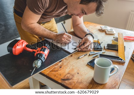 Man making draft plan using pencil on the table with tools #620679029