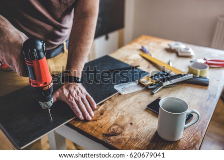 Man drilling laminate with power drill on the table #620679041