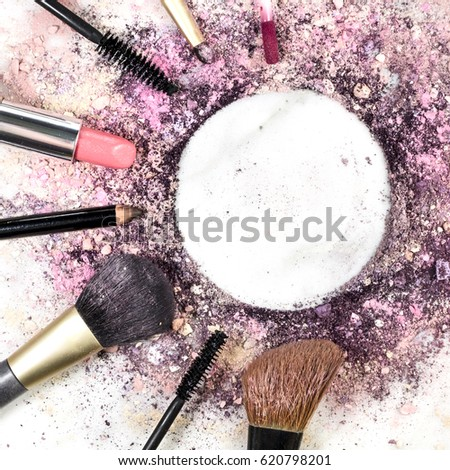 Makeup brushes, pencil, lipstick and other objects, forming a frame on a light background, with crushed powder and copy space. A square template for a makeup artist's business card or flyer design