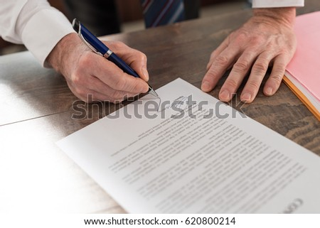 Businessman signing a document in office #620800214