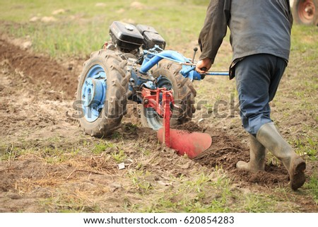 A man plows a field with a motor-block. #620854283