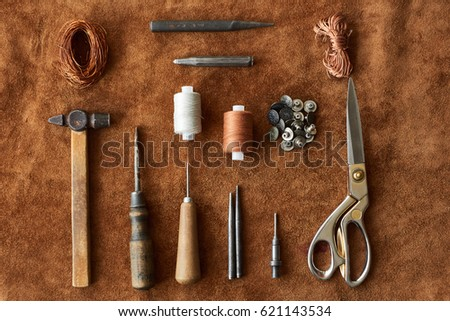 Artisan tools for working with leather: hammer, scissors, thick thread, metal wire, awl, buttons top view on leather background Royalty-Free Stock Photo #621143534