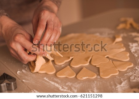 Woman making heart shape cookies from batter on table closeup. Selective focus.  #621151298