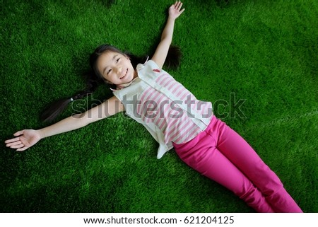 Long haired girl lying on artificial grass #621204125